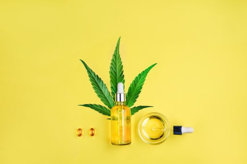Bottle with CBD oil, pipette, capsules and cannabis leaf on a yellow background. Minimalism, flat lay.